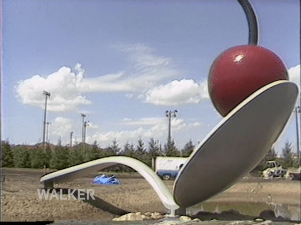 Still from U-matic tape digitized by BAVC PReservation of the 1988 installation of Spoonbridge and Cherry at the Walker Art Center