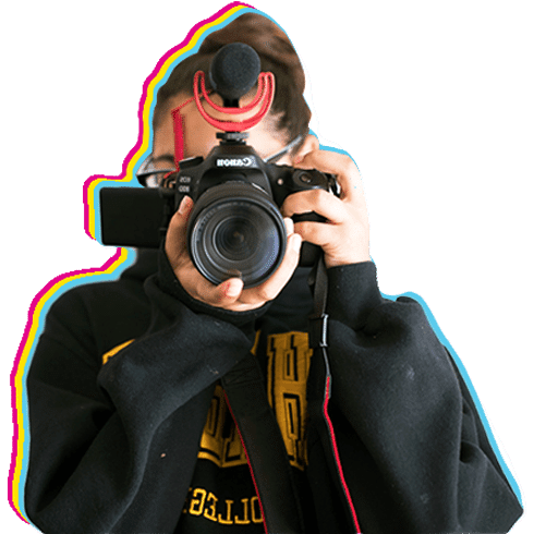 Reel Stories student looks into DSLR viewfinder and point their lens straight ahead